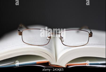 A pair of reading glasses on top of a book - Stock Photo