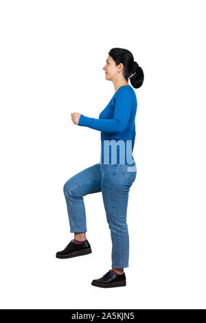 Full length side view of motivated, confident young woman climbing a imaginative staircase isolated on white. Concept of career development, success a - Stock Photo
