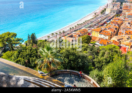 A female tourist on Castle Hill relaxes on a deck under the waterfall and above the Old Town, beach and promenade of Nice, France. - Stock Photo