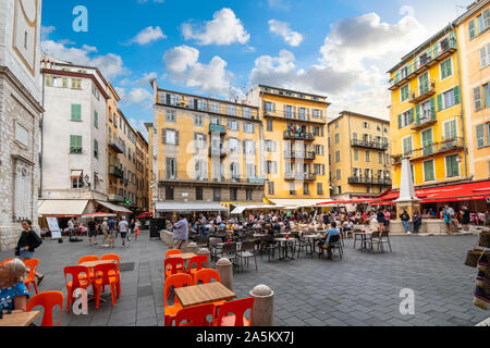 Tourists enjoy a late afternoon at the shops and cafes at Place Rossetti in Old Town Nice, on the French Riviera - Stock Photo