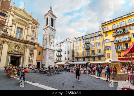 Tourists enjoy an early evening in Place Rossetti surrounded by shops, cafes, fountains and the Nice Cathedral, in Old Town Nice France. - Stock Photo