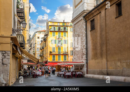 Tourists enjoy a lively late afternoon at the shops and cafes in Place Rossetti, in the old town center of Nice, France, on the French Riviera. - Stock Photo