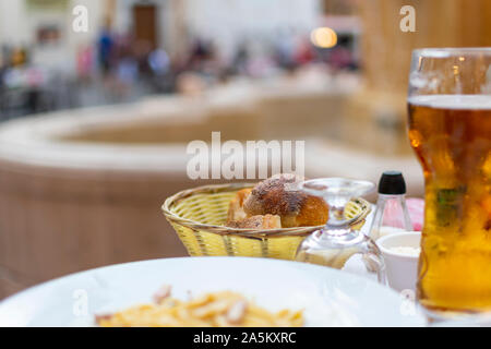 A bread basket of freshly baked rolls on a patio table in a piazza at Place Rossetti on the French Riviera in Nice, France. - Stock Photo