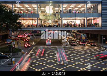 Traffic passes under the Apple flagship store at the IFC Mall on Lung Wo Road in the Central District of Hong Kong. - Stock Photo