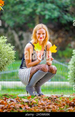 Mid-adult young woman blonde fairhair squatting amongst Autumn Fall fallen leaves in park and hand hands holding two leaves looking at camera eyeshot - Stock Photo