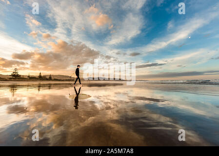 Teen with surfboard on a beach in New Zealand at sunset
