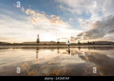 Teen boy with surfboard walking on a beach at sunset