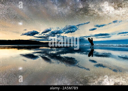 Silhouette boy holding surfboard walking on beach under starry sky with reflection