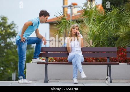 Endless chat female teenager long lengthy neverending talking on smartphone while her boyfriend friend waits nervously cellular-phone - Stock Photo