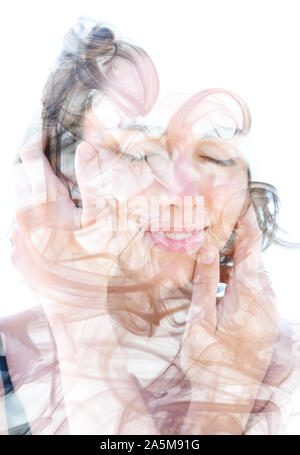 Double exposure. Photograph of smoke combined with a close up profile portrait of a beautiful young girl with hands gently caressing her face and chee - Stock Photo