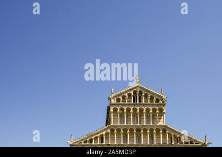 Top exterior of the façade of Pisa Cathedral (Duomo di Santa Maria Assunta) in the famous Piazza dei Miracoli against clear blue sky, Tuscany, Italy - Stock Photo