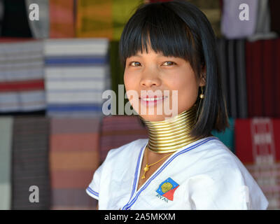 """Young Myanmarese Kayan Lahwi longneck woman (""""giraffe woman"""") with tribal Padaung brass neck rings/coils smiles for the camera."""