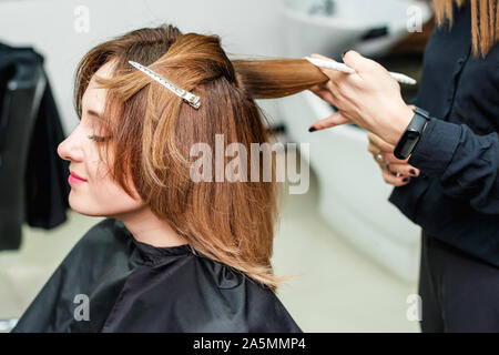 Woman hairdresser is making hairstyle to red hair girl in beauty salon. The process of hair styling in the hairdressing salon.