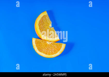 Orange fruit slides on a blue background - Stock Photo