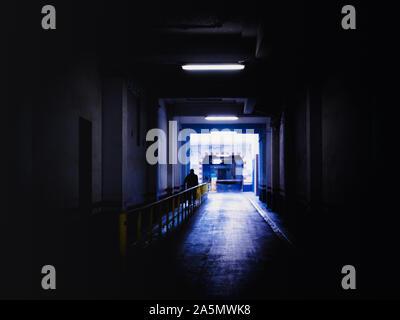 Defocused man silhouette walking through a dark tunnel in Barcelona, Spain - Stock Photo
