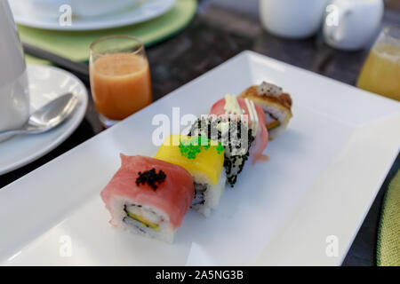 Sushi roll in luxury hotel breakfast buffet, restaurant interior - Stock Photo