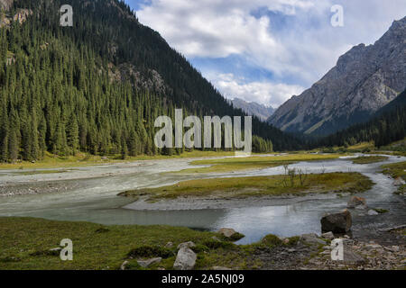 Idyllic summer landscape with hiking trail in the mountains with beautiful fresh green mountain pastures and snow-capped mountain tops - Stock Photo