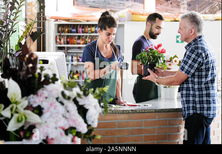Customer Buying Plant And Sales Clerk Scanning Barcode - Stock Photo