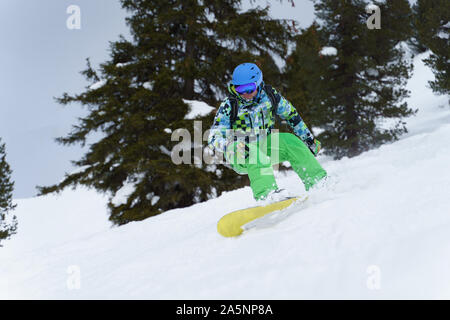 Male snowboarder riding on mountainside on background of trees in afternoon - Stock Photo