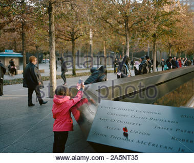 Girl trying to put a USA flag on the National September 11 Memorial, New York City - Stock Photo