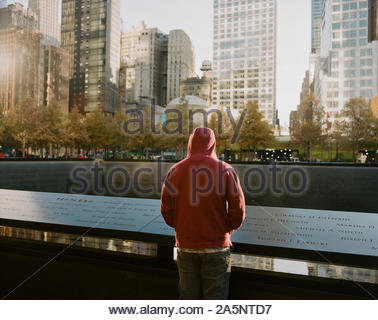 Man watching the northern pool of the National September 11 Memorial, New York City - Stock Photo