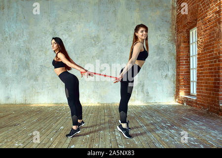 Two young women are doing paired exercises in the fitness room. posing and smiling at the camera, have fun, great atmosphere beautiful light, fitness - Stock Photo