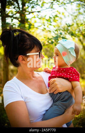 One year old baby girl hold by mother in nature - Stock Photo