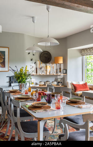 White pendant lights above dining table  with windowseat. - Stock Photo