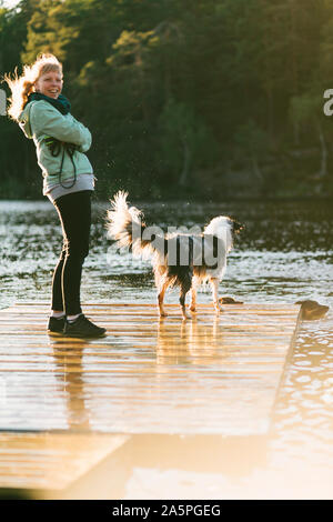 Woman with dog on jetty - Stock Photo