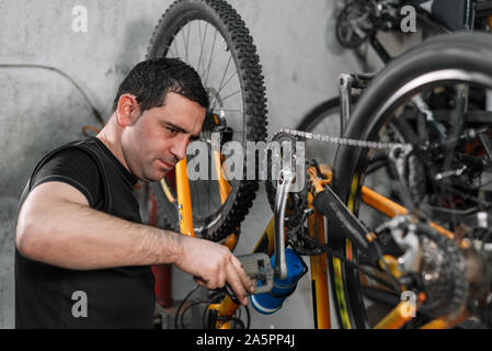 Bicycle mechanic in a workshop in the repair process . - Stock Photo