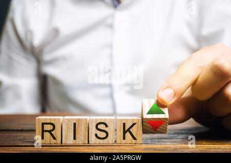 Businessman puts wooden blocks with the word Risk and up and down arrows. Business risk management concept. Forecasting and planning. Risks assessment Stock Photo