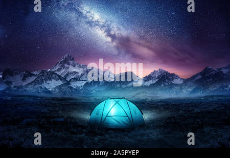 Camping in the mountains under the stars. A tent pitched up and glowing under the milky way. Photo composite. - Stock Photo