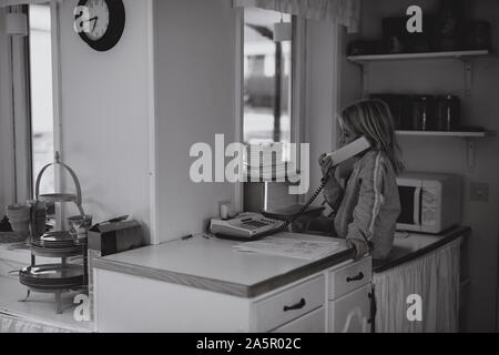 Girl using cable phone in kitchen - Stock Photo