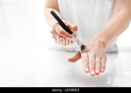 Hand spa. The woman puts a mask on the skin of the hand. Hand skin care. - Stock Photo
