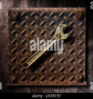 Old rusty wrench on rusting diamond plate steel artistic fine art - Stock Photo