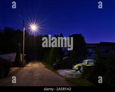 Car and street light in empty alley at dusk - Stock Photo