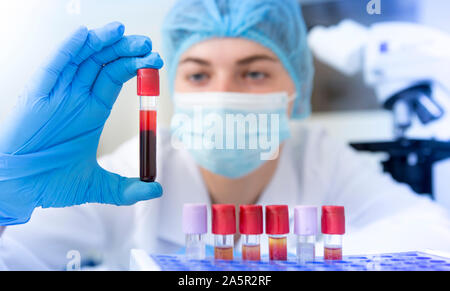 Woman scientist holding blood sample tube from a rack - Stock Photo
