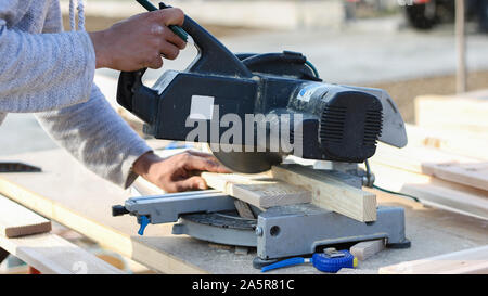 worker cutting wood with circular saw (softwood) - Stock Photo