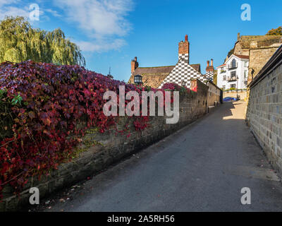 Creeper turning red in autumn on a wall at the old Manor House on Waterside Knaresborough North Yorkshire England