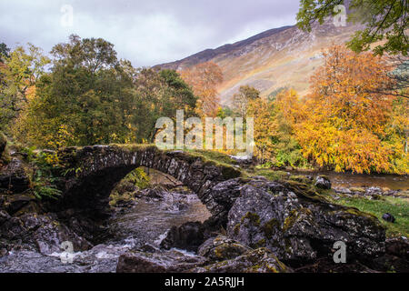 Old curved Roman Bridge in Glen Lyon, Scottish Highlands with rainbow on hills in background - Stock Photo