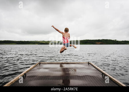 Little Girl Jumps off Dock into Lake on a Cloudy Summer Day - Stock Photo
