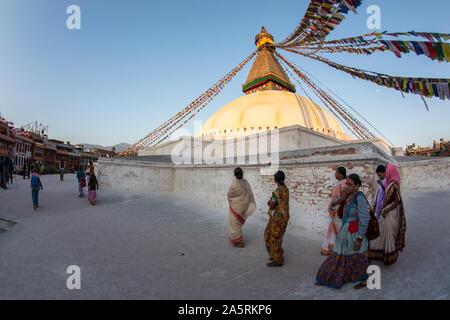 Buddhist devotees visit Boudhanath Stupa in Kathmandu, Nepal at sunset - Stock Photo