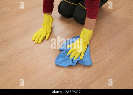 Adult woman kneeling and cleaning laminate floor using rag - Stock Photo
