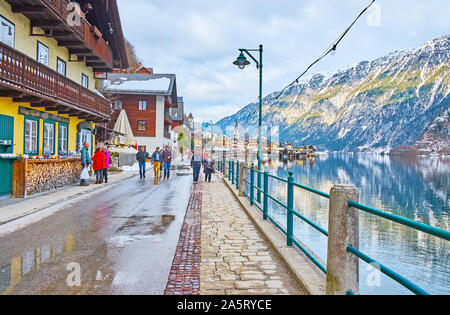 HALLSTATT, AUSTRIA - FEBRUARY 25, 2019: The wet winter weather in old town; lakeside promenade is covered with puddles and melting snow, on February 2