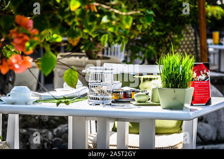 laid breakfast table with placemats and white linen napkins and cutlery in a beautiful garden - Stock Photo