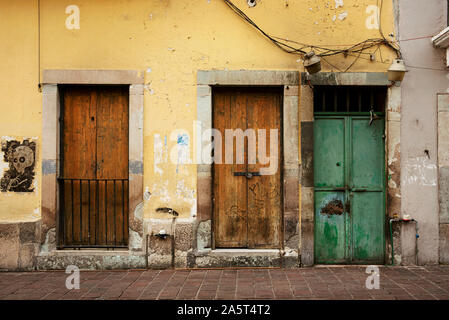 Decaying facade of building with wooden doors in the historic centre of Guanajuato, Mexico. Jun 2019 - Stock Photo