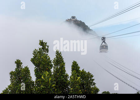 Beautiful landscape of the cable car moving into clouds seen from Morro da Urca in the Sugar Loaf Mountain in Rio de Janeiro, Brazil - Stock Photo