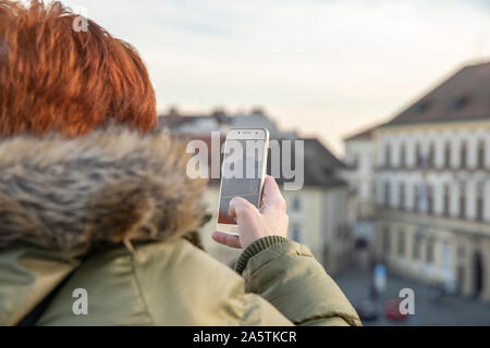 woman is looking at Brno from a viewing terrace. Take pictures of the city on the phone and share it on the social site - Stock Photo