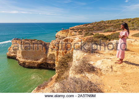 Algarve coast towards Faro from the cliffs above Praia da Marinha, Portugal attractive young black woman admiring the view from cliff - Stock Photo