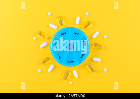 different nutritional supplements for one week and a pills box on yellow background - Stock Photo